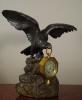 Een bronzen adelaar horlogestandaard met koetshorloge met kwartierrepetitie
