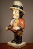 Een kleurrijk houten beeldje van gebochelde man met prominente knopen op jas, omstreeks 1850