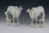 A pair of white cows with milkers in Dutch delftware