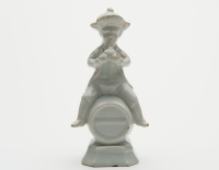 A White Figure of a Fellow Seated on a Barrel in Dutch Delftware