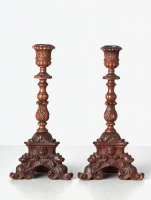 A small pair of Italian highly carved walnut single candlesticks, circa 1850