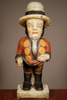 A multicoloured carved sculpture of a hunchback with remarkable buttons on his jacket, circa 1850