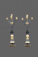 A pair of fire-gilded and patinated French Empire four-light candlesticks