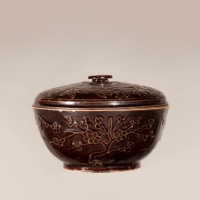A very unusual Chinese porcelain bowl and cover with thread relief design of prunus under a deep brown glaze.