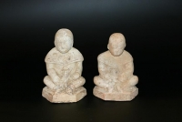 Two ceramic sitting boys with animals