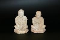 Aardewerk sculpturen van zittende jongens met dier