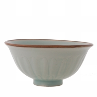 Chinese porcelain bowl with carved petals on the exterior, the interior with a carved and combed design of a water bird in a lotus pond, all under a fine pale blue glaze.
