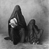 Two women, wearing black, with bread, Morocco 1971