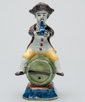 A Polychrome Figure of a Fellow Seated on a Barrel in Dutch Delftware