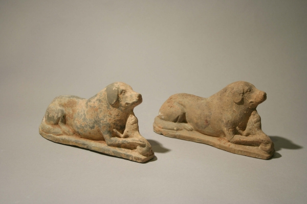 A pair of pottery recumbent hounds