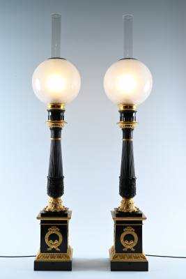 A pair of ormolu and patineted  oil lamps