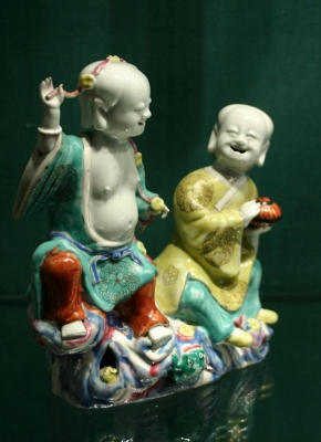 A porcelain sculpture of the laughing twins famille rose Chinese