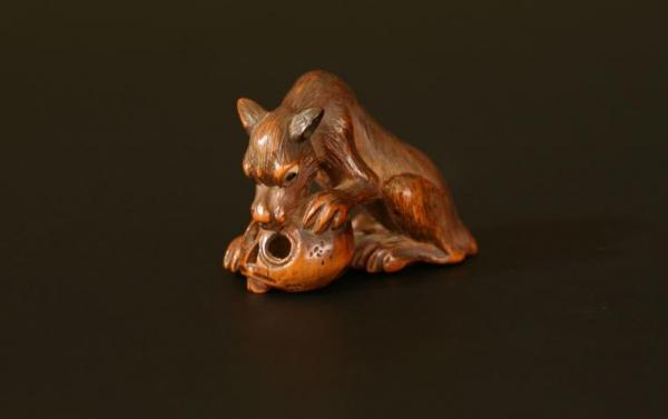 Houten netsuke: wolf met schedel