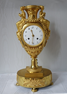 A fine and rare ormolu urn mantel clock, cupid and classical draped female figures holding flowers strands, France Directoire ca. 1795-1800.