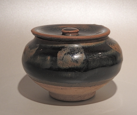 A Chinese stoneware small jar with its countersunk cover, the blackish glaze with russet splashes.