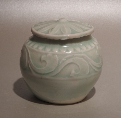 A Chinese porcelain jarlet and cover with a carved design of stylized waves under the pale blue glaze.