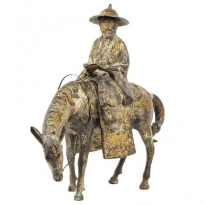 A CHINESE GILT-BRONZE SCULPTURE OF A SCHOLAR RIDING A HORSE